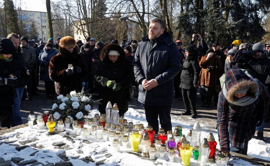 Adrian Zandberg przy pomniku ofiar wojen i represji w Hajnówce