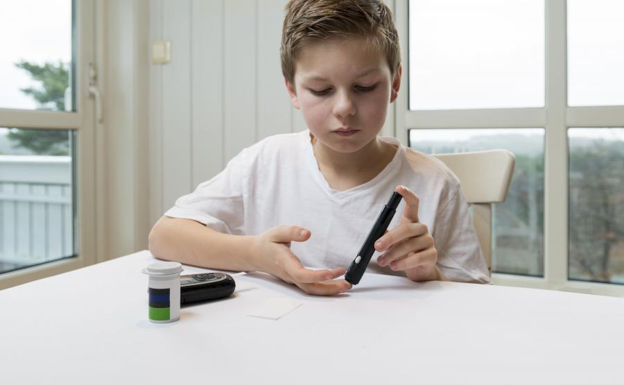Chłopiec mierzy sobie poziom glukozy we krwi