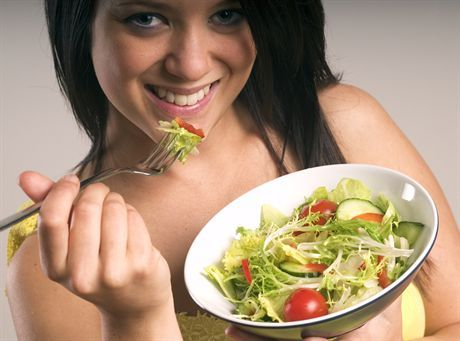Young woman stood with a bowl of mixed salad containing iceberg lettuce,cherry tomatoes,cucumber,frisee,radish and sliced red peppers.