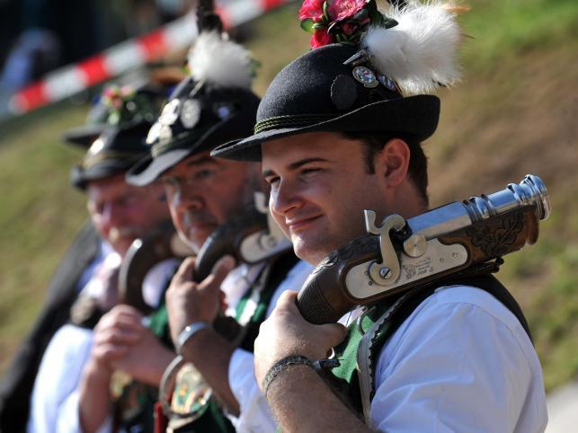 Mężczyźni ubrani w tradycyjne stroje szykują się na oddanie salwy oznajmiającej koniec Oktoberfest