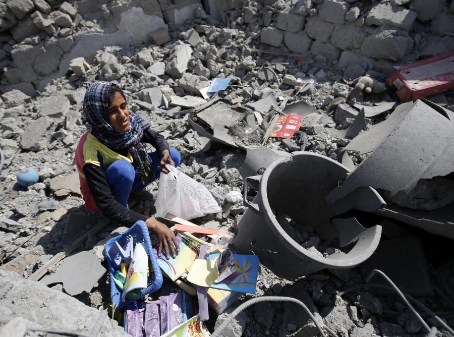Palestyńska dziewczynka zbiera przybory szkolne w ruinach domu w Strefie Gazy