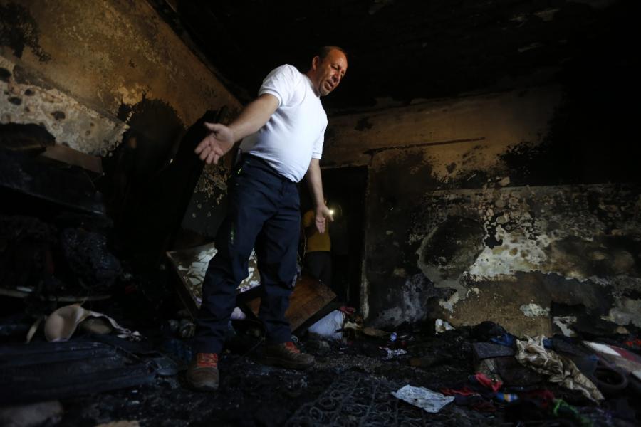 Mężczyzna na miejscu palestyńskiego domu spalonego przez żydowskich osadników, Nablus, Zachodni Brzeg Jordanu