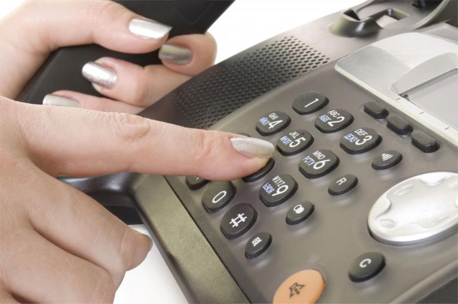 Kobieta wybiera numer w telefonie stacjonarnym