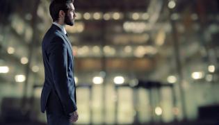 Mężczyzna w garniturze na tle biurowca