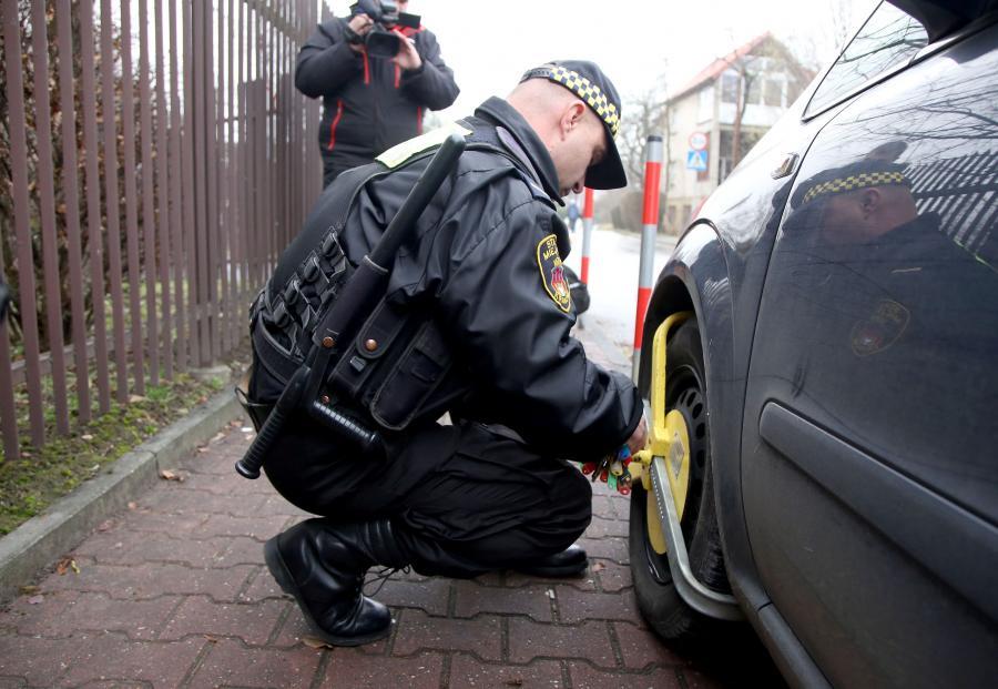 Straż miejska zakłada blokadę na źle zaparkowany samochód na ulicy Turystycznej w Krakowie
