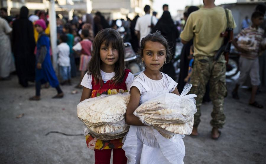 Dziewczynki z Aleppo niosące dary pomocy humanitarnej