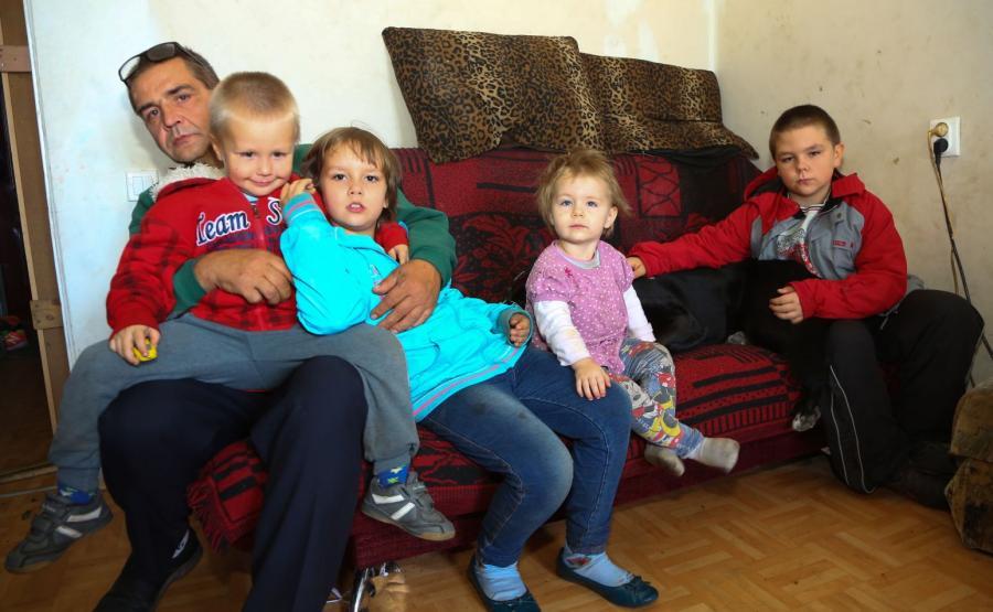 Pan Wojciech ze swoimi dziećmi w ich mieszkaniu w Łodzi