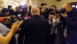 Oskarżony Piotr R. (tyłem) rozmawia z dziennikarzami na korytarzu sądowym