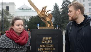 Adrian Zandberg i Julia Zimmermann podczas happeningu Partii Razem zorganizowanym przed Sejmem. Politycy Partii Razem ustawili pomnik - złotą piłę do cięcia drzewa - dedykowany ministrowi środowiska